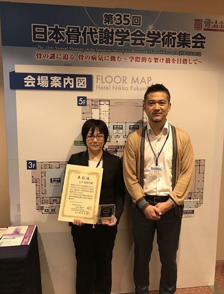 受賞した山下美智子さん(左)、プロテオサイエンスセンター・病態生理解析部門 今井祐記教授(右)の写真です